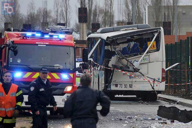 A French police officer stands near the wreckage of a school minibus after it crashed into a truck near Rochefort.